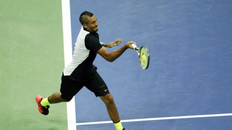 Nick Kyrgios, of Australia, returns a shot to Andy Murray, of Britain, during the first round of the U.S. Open tennis tournament in New York, Tuesday, Sept. 1, 2015. (AP Photo/Julio Cortez)