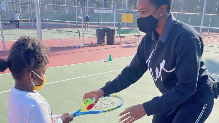 40 Love Founder Doris Obih helps young girl during tennis lesson.