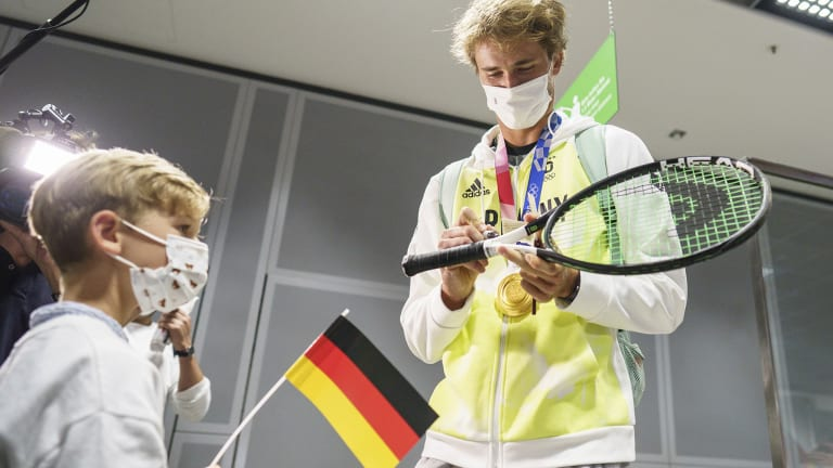 Zverev signs an autograph for a young supporter who showed up to greet the Olympic champion.